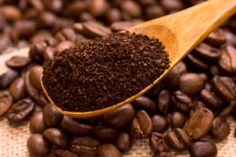 scoop of ground coffee above coffee beans